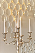 Burning candles in a candle holder against a wall decoration with porcelain, Rosenthal Casino, Selb