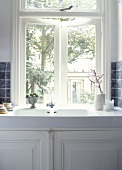 An antique porcelain sink under the window with a white cupboard underneath