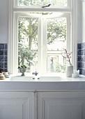 Antikes Spülbecken aus Porzellan mit weißem Unterschrank unter dem Fenster