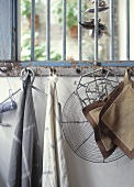 Tea towels, pan holders and other kitchen utensils hanging from a rusty bar with hooks