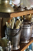Knives and forks in a silver pot on a wooden shelf