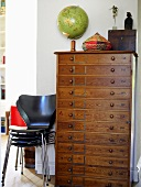 A globe on top of a chest of drawers with a stack of butterfly chairs beside it