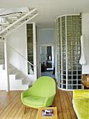 Ein grüner Sessel neben dem Treppenaufgang im Wohnzimmer
