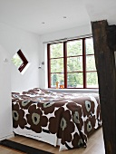 A double bed with a brown patterned quilt in a bedroom