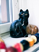 A cat ornament on a window sill
