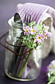 Cutlery and napkins in a jar with a handle decorated with baby primroses