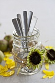 A glass of cutlery decorated with sunflower seed heads