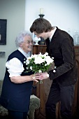 A grandson giving his grandmother a bunch of flowers for her birthday