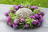A wreath of clover flowers with green elderberries and a stone