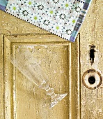 An Empty Elegant Glass on a Rustic Door with a Floral Napkin