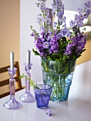 A blue glass vases of purple and pink summer flowers and two candles
