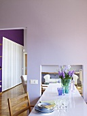 A long dining table in a high dining room with pink walls