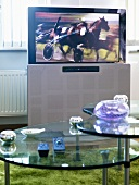 A flat screen television behind a glass coffee table