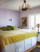 Ein Doppelbett, darunter Bettkasten mit Milchglasfronten in einem einfachen Schlafzimmer