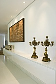 Two antique candlesticks on a long sideboard in a white hallway