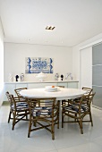 A round dining table and chairs in a dining room with an azulejo