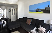 A large canvas picture above a black sofa