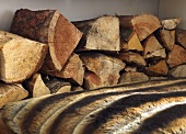 A stack of firewood for a fireplace behind a fur rug