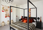 Decorative cushions and a quilt on a bed on a four poster bed and a kimono hanging on the wall in a bedroom