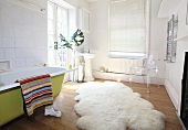 A sheepskin rug in front a green, free-standing bathtub