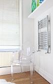 A Philippe Starck chair next to a towel rail in a bathroom