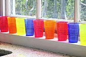 Colourful plastic cups on a window sill