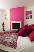 A double bed in a bedroom with pink and white walls