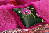 Pink decorative cushions on a bed