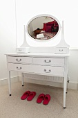 A white make-up table with an oval mirror and two pairs of pink slippers