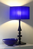 A table lamp with a blue shade next to a blue glass bowl