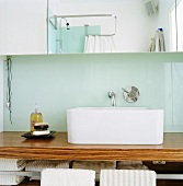 A wooden washstand with a square wash basin