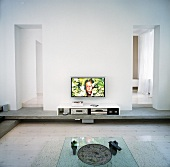 A glass coffee table, a low sideboard with multimedia devices inside and a flat-screen television on the wall
