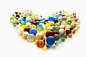 Colourful glass marbles arranged in a heart shape