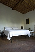 A high double bed with white bedclothes in a bedroom with a terracotta floor and a wood beam ceiling
