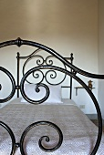 A bed with a wrought iron frame