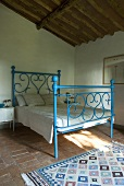 A blue wrought iron bed in a bedroom with a terracotta floor