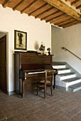 A piano next to a flight of steps in an entrance hall with a terracotta floor