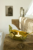 A tealight on a dried leaf on a wooden beam