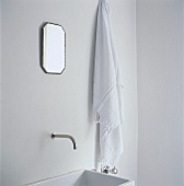 A towel hanging next to a wash basin