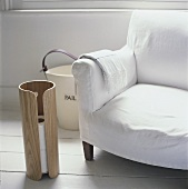 A white-covered armchair next to a toilet paper holder and a bucket