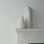weiße Vasen und eine Kette auf einem Regal