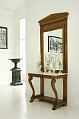 An antique wall table with a large mirror