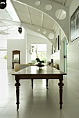 A long wooden table from the 18th century in a room with metal construction elements
