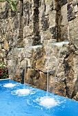 A pool with mini waterfalls coming from a natural stone wall