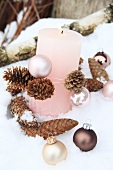 A pink candle with pine cones and Christmas baubles in the snow