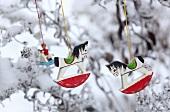 Kleine Schaukelpferde aus Holz hängen an einem verschneiten Baum