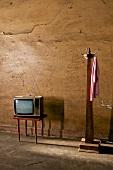 alter Fernseher auf Tischchen, neben Garderobenständer aus Holz
