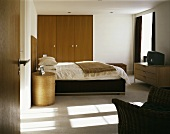 View through an open door into a modern bedroom with a double bed and built-in wooden closet
