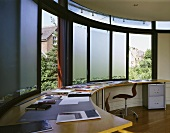 A modern home office with a built in desk in front of a curved window bank