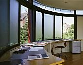 Modernes Home Office mit angefertigtem Arbeitstisch vor geschwungener Fensterfront